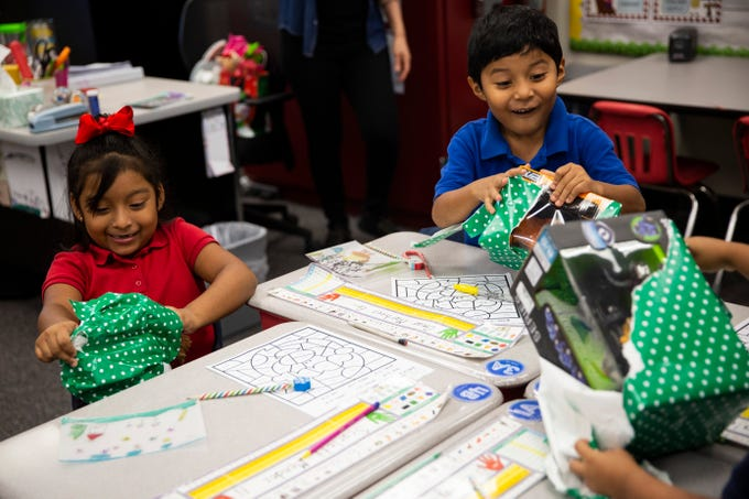 First graders Scarlett Mendez, left, and Omar Martinez-Gomez, right, unwrap toys donated by Empowered Latinos on Thursday, December 20, 2018, at Bonita Springs Elementary School in Bonita Springs. Empowered Latinos collected most of the toys at a charity concert they organized, where attendees could donate a new toy in lieu of paying a cover charge.