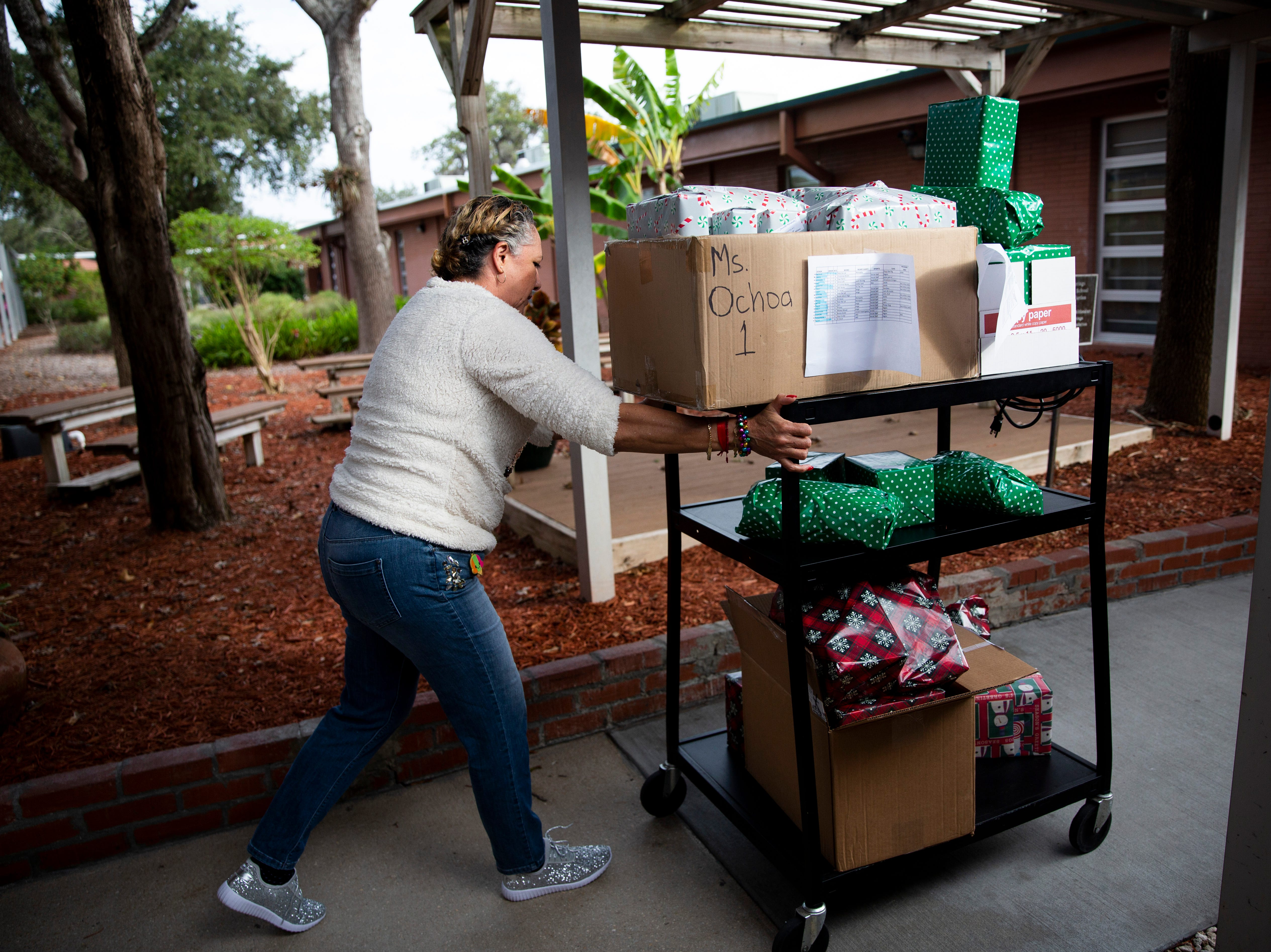 Marta Romero pushes a cart full of toys donated by Empowered Latinos on Thursday, December 20, 2018, at Bonita Springs Elementary School in Bonita Springs.