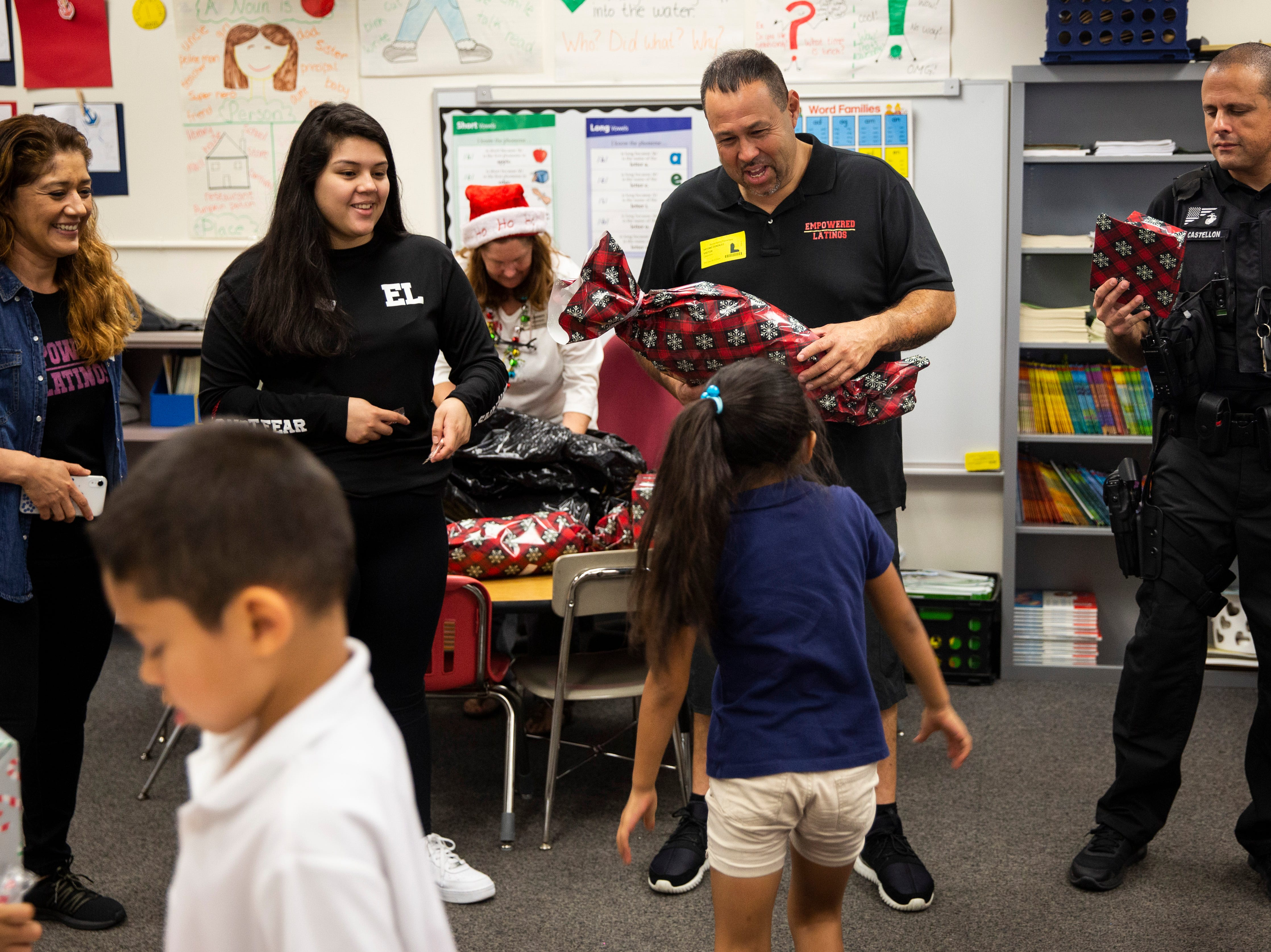 From left to right, Juanita Gonzalez, Rosemary Gonzalez, and Tony Gonzalez, from Empowered Latinos, along with Richard Castellon, K-9 handler with the Lee County Sheriff's Office, distribute toys to students on Thursday, December 20, 2018, at Bonita Springs Elementary School in Bonita Springs.