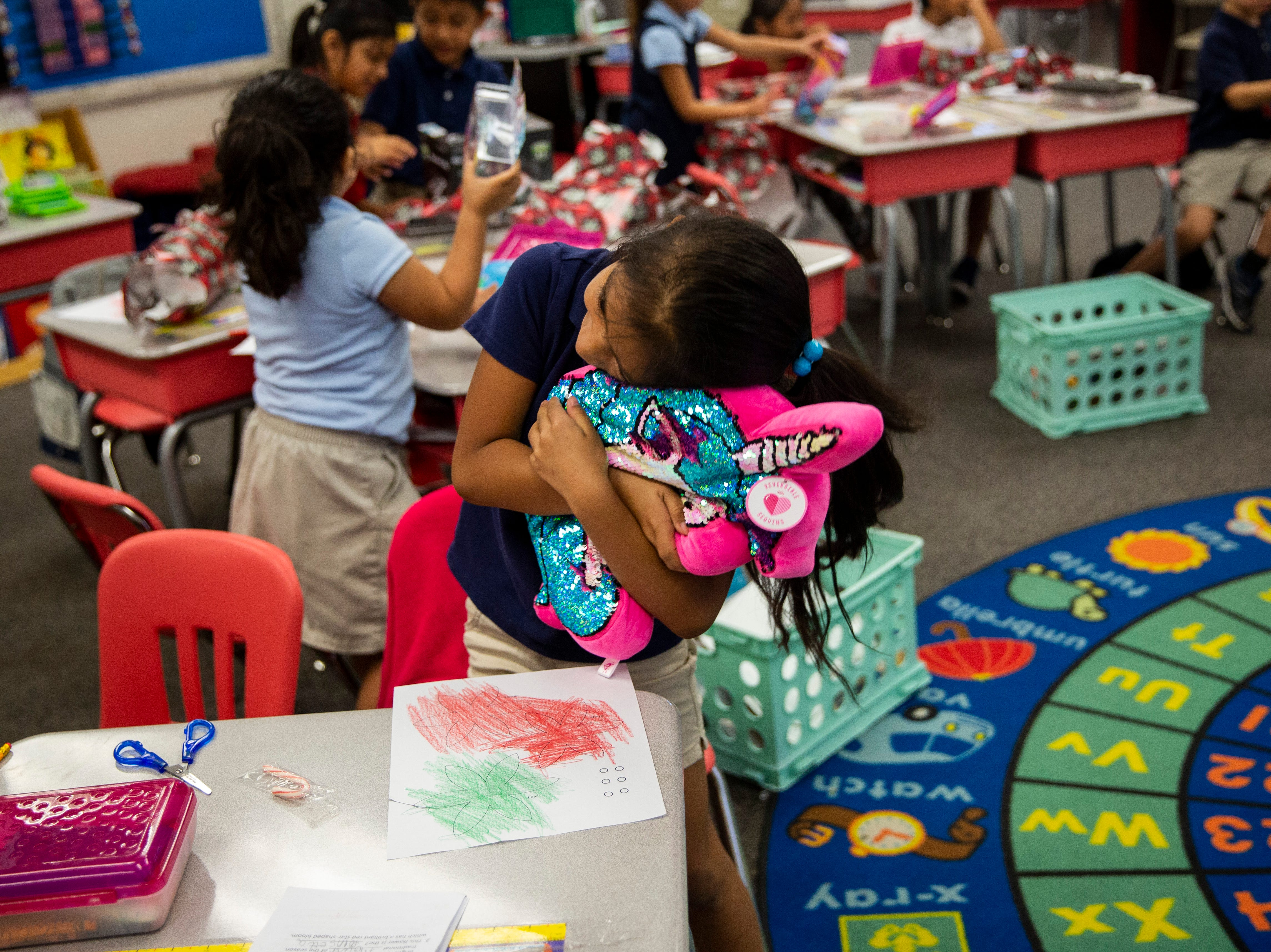 First grader Alyson Vicente hugs her new unicorn pillow, donated by Empowered Latinos, on Thursday, December 20, 2018, at Bonita Springs Elementary School in Bonita Springs.