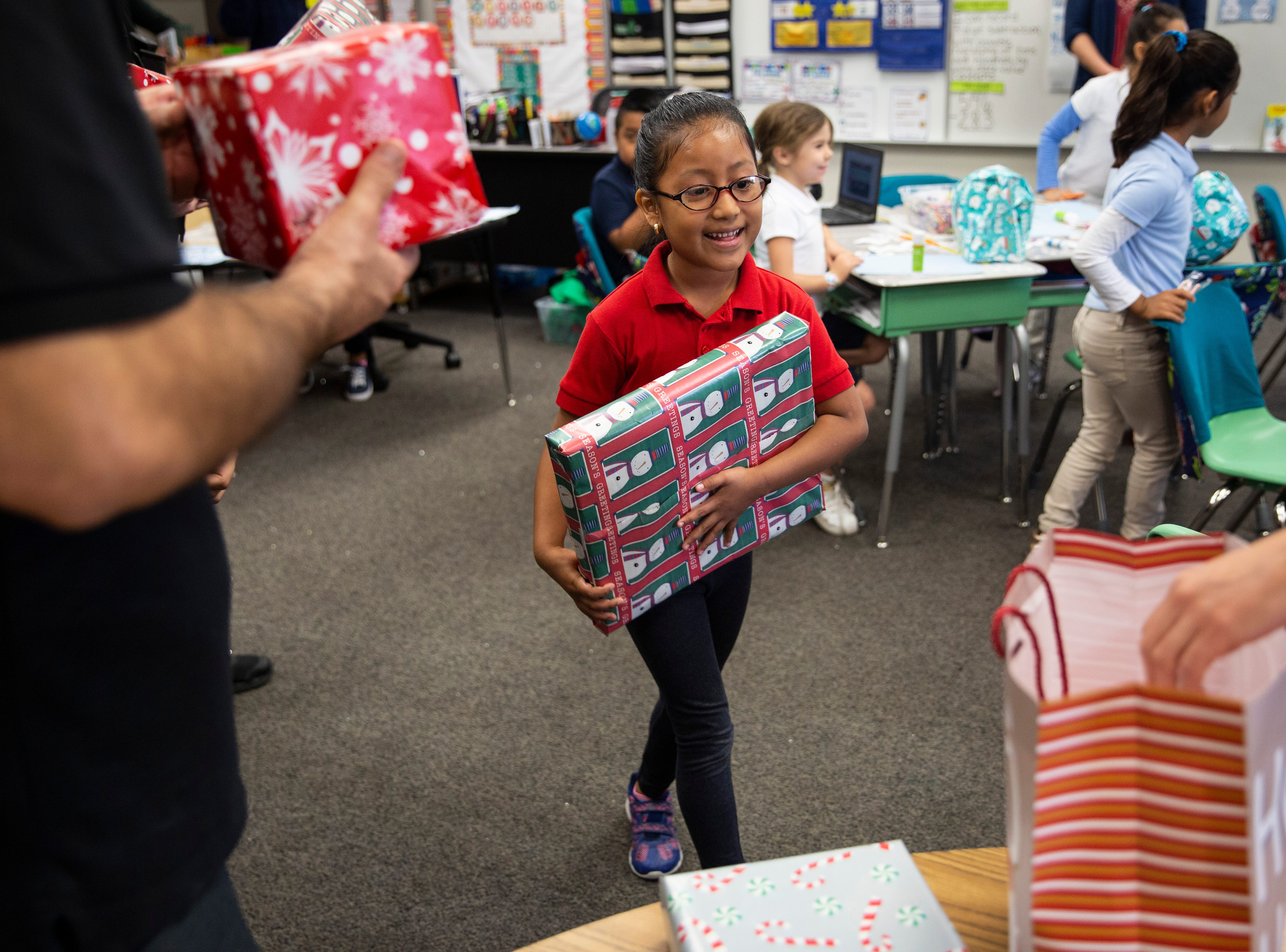 Students in Christine Dore-Smith's first grade class receive toys donated by Empowered Latinos on Thursday, December 20, 2018, at Bonita Springs Elementary School in Bonita Springs.