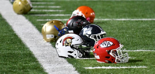 High School Football Helmets from school across the nation laying on the field  during the FBU Freshman All-American football game at Gulf Coast High School in Naples, Wednesday, Dec. 19, 2018.