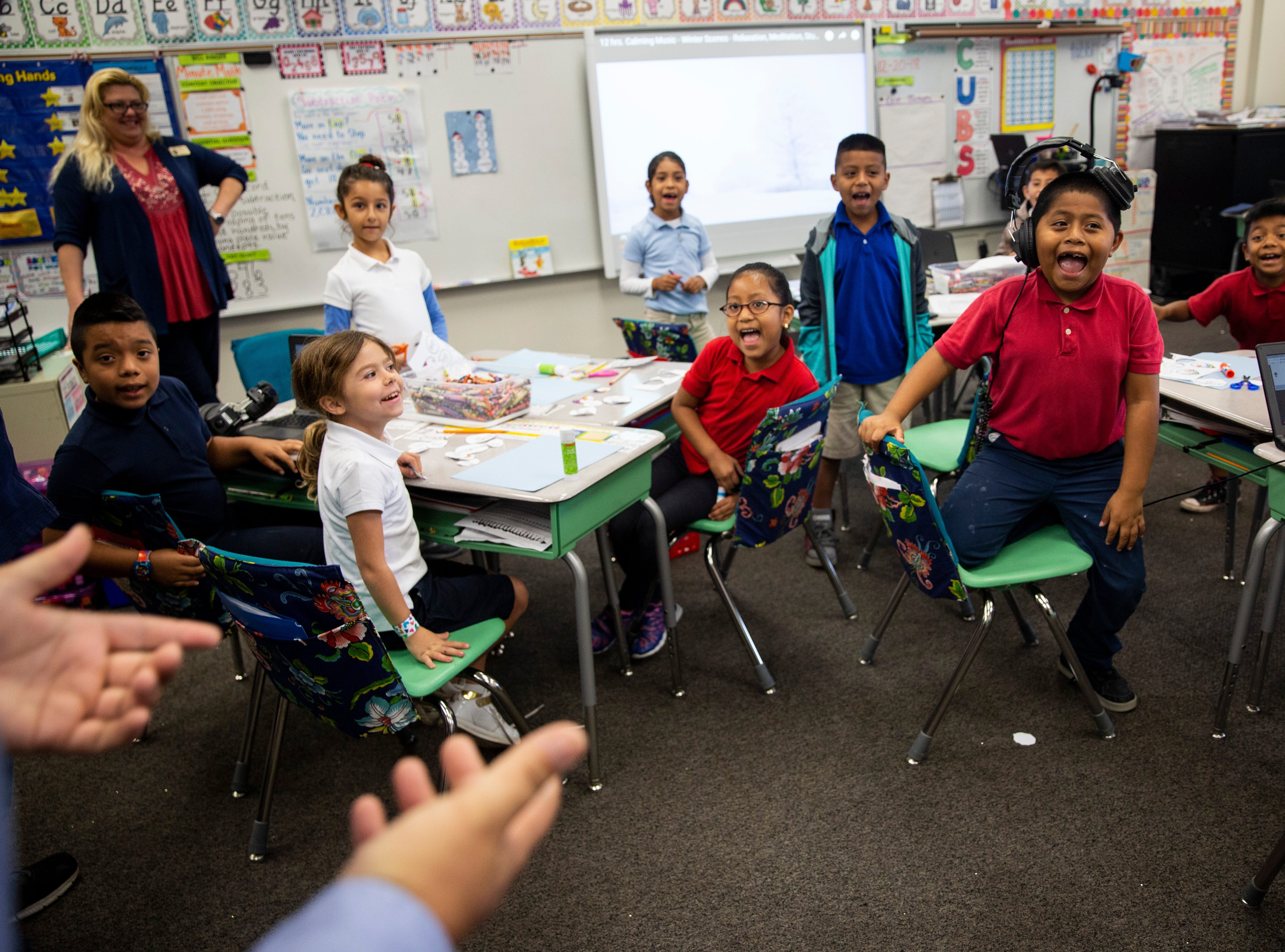 Students in Christine Dore-Smith's first grade class cheer as Principal Rob Cooper tells them about the toys they'll be receiving, donated by Empowered Latinos, on Thursday, December 20, 2018, at Bonita Springs Elementary School in Bonita Springs.
