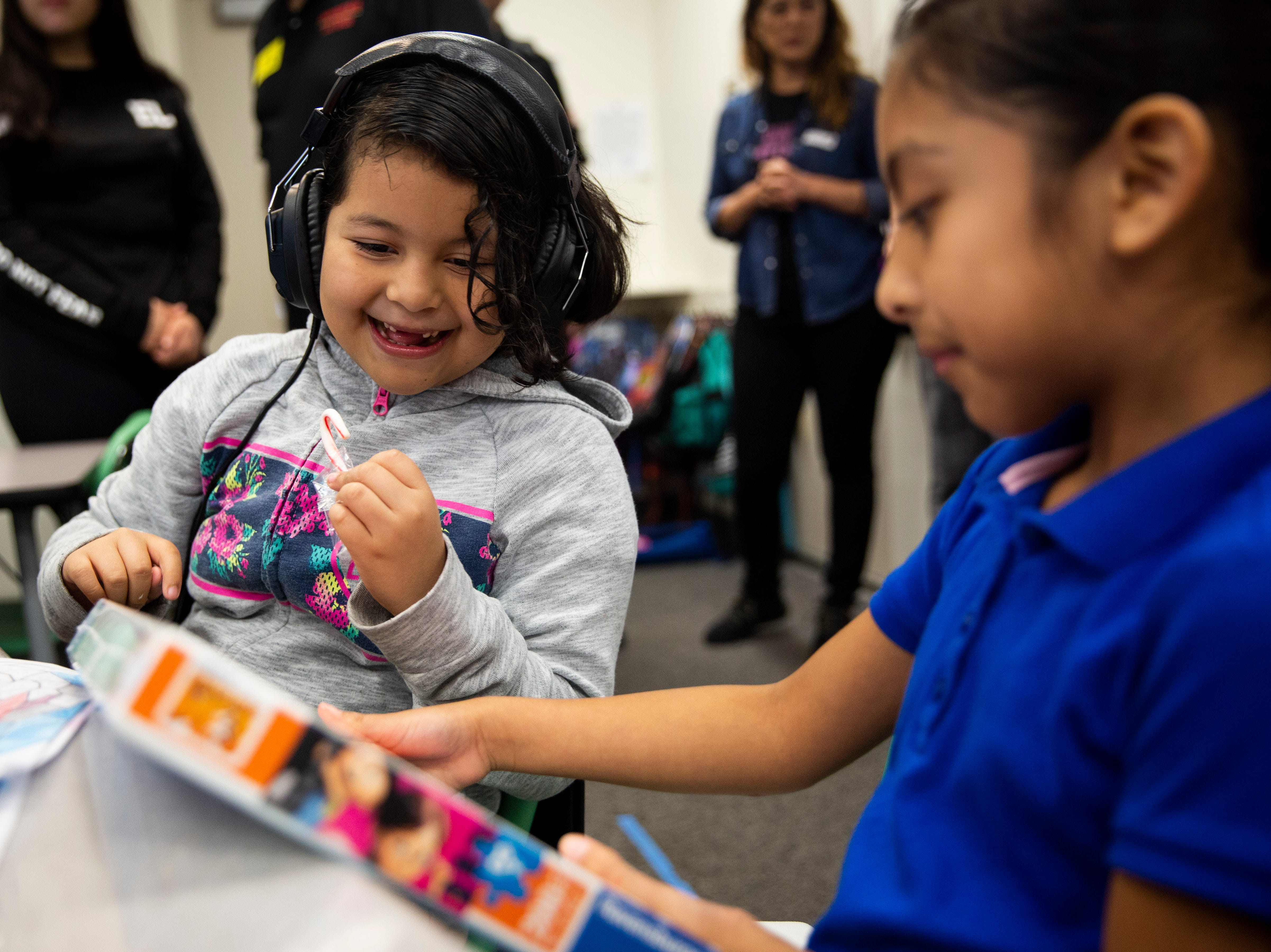 Second graders Helen Chaperno, left, and Diana Gonzales-Lopez, right, show each other their new toys donated by Empowered Latinos on Thursday, December 20, 2018, at Bonita Springs Elementary School in Bonita Springs.