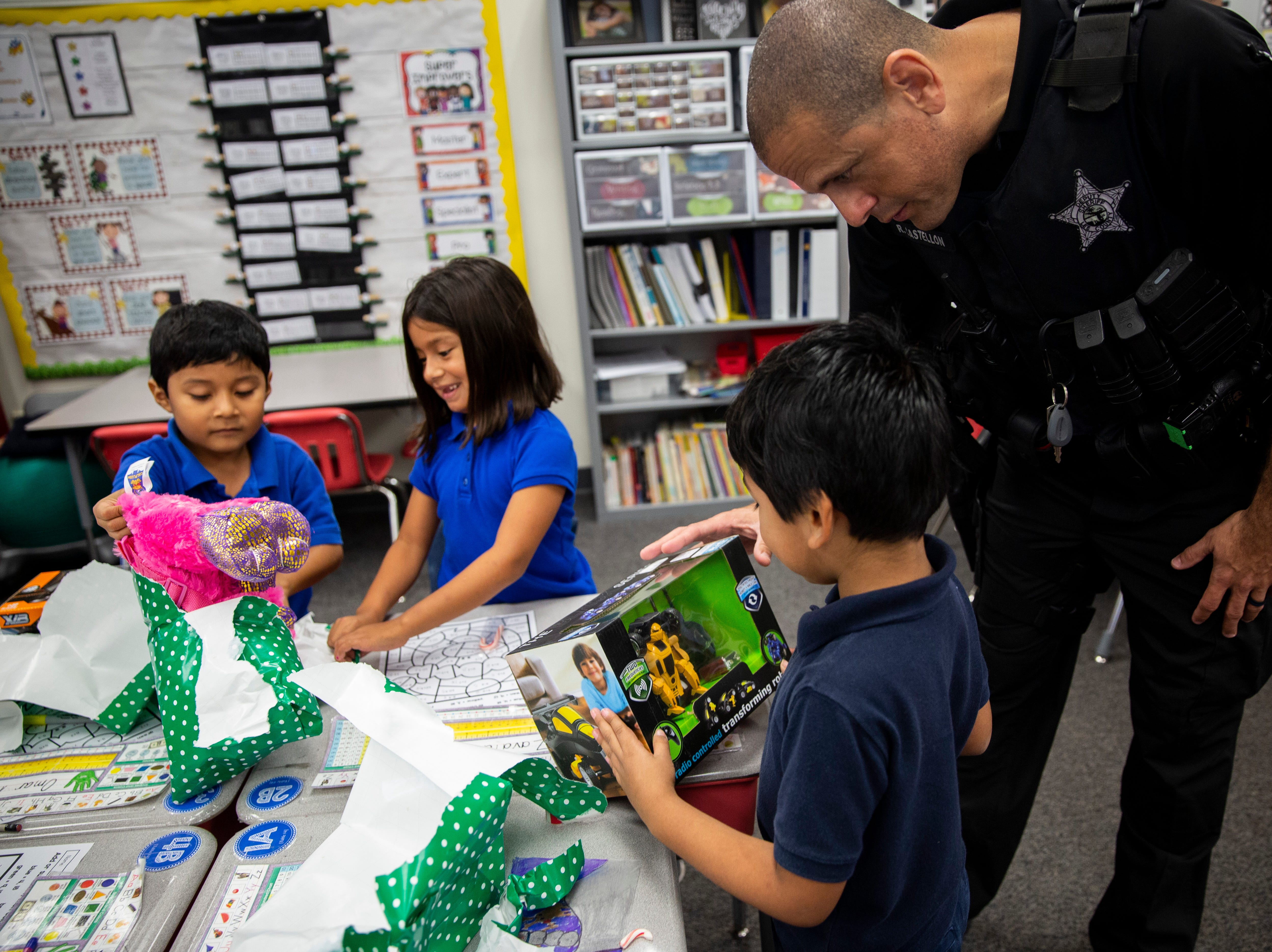 Richard Castellon, K-9 handler with the Lee County Sheriff's Office, talks to Christopher Mendez, Ramirez about his new toy donated by Empowered Latinos on Thursday, December 20, 2018, at Bonita Springs Elementary School in Bonita Springs.