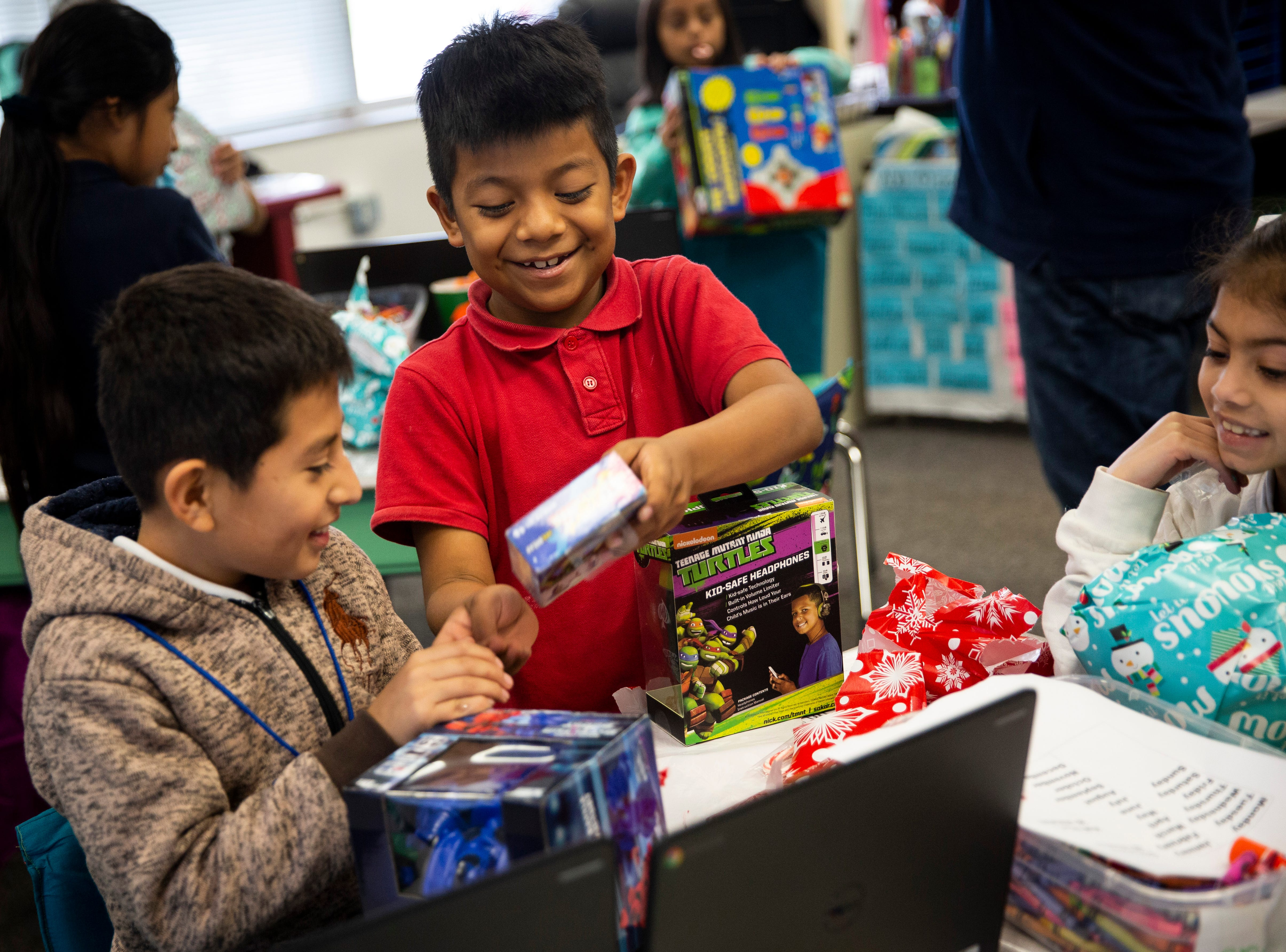 Students in Christine Dore-Smith's first grade class show each other their new toys donated by Empowered Latinos on Thursday, December 20, 2018, at Bonita Springs Elementary School in Bonita Springs.
