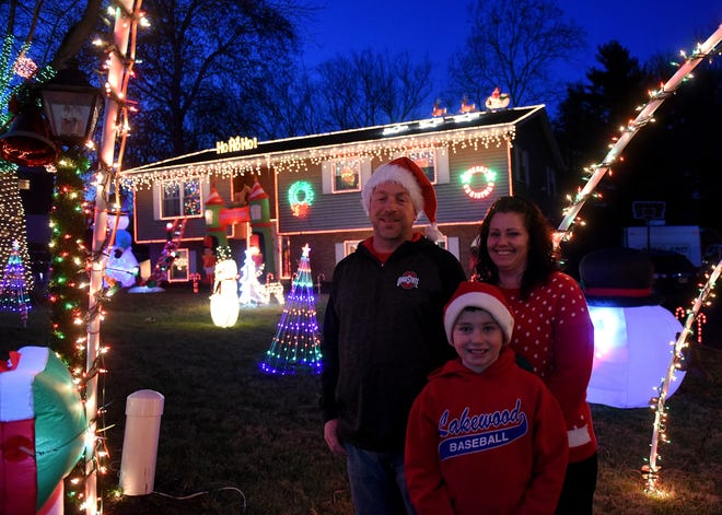 Kenny Riley, Jessica Kirk and nine-year-old Tegan pose in front of their homes Christmas lights display. The home has been voted as best lights display in the county by Advocate readers.