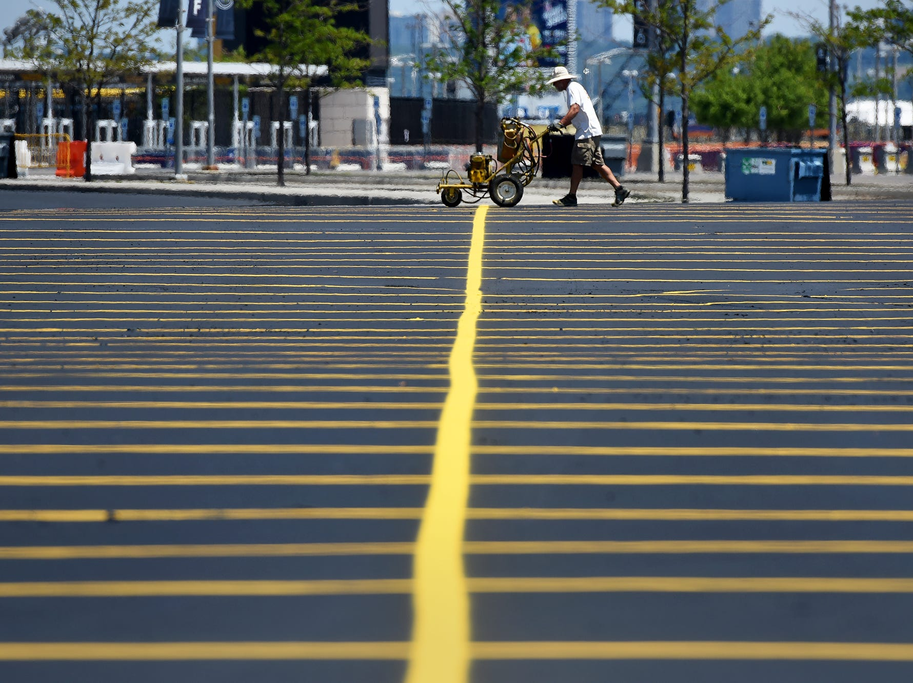 Steam rises off the pavement while as new lines are painted in the parking lot of MetLife Stadium on Wednesday, July 18, 2018.