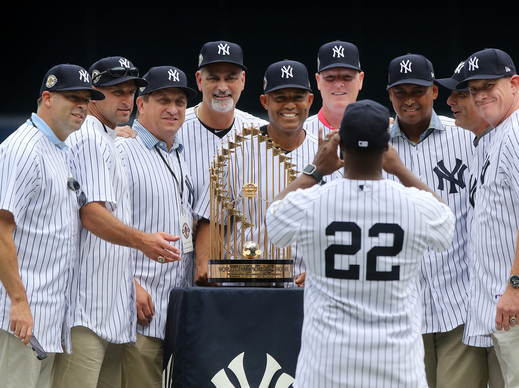 Members of the 1998 Yankee bullpen pose for a photo taken by Homer Bush with the MLB championship trophy.Pedota POY 2018