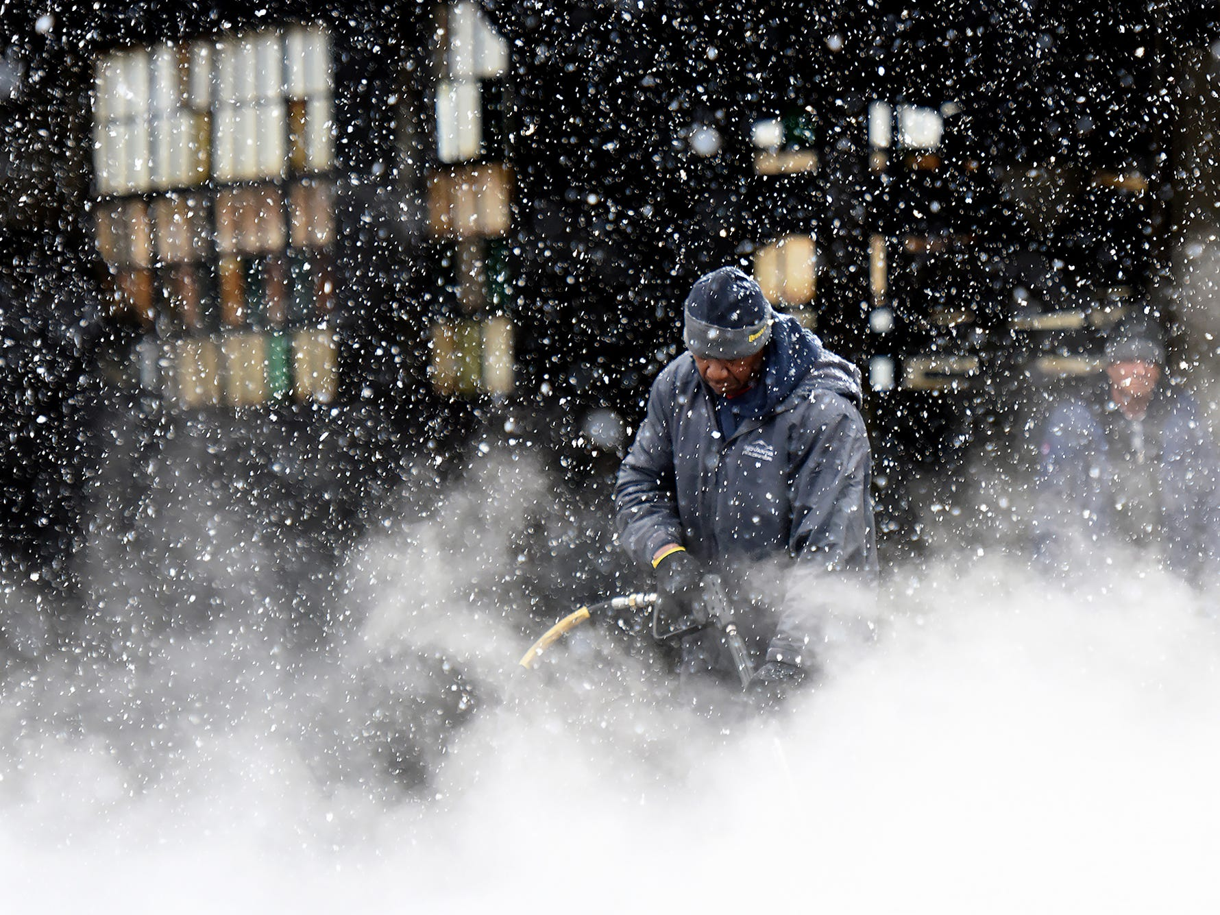 An employee power washes the yard at a business on Market St. in Paterson taking advantage of a slow day with no deliveries on Wednesday, March 7, 2018.