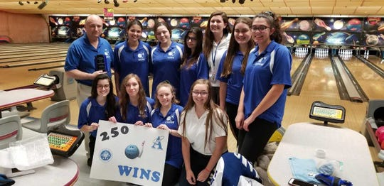 The Holy Angels bowling team celebrates coach Patrick Dunne's 250th win after defeating rival Immaculate Heart, 7-0, in a Big North United girls match on Monday, Dec. 17, 2018.