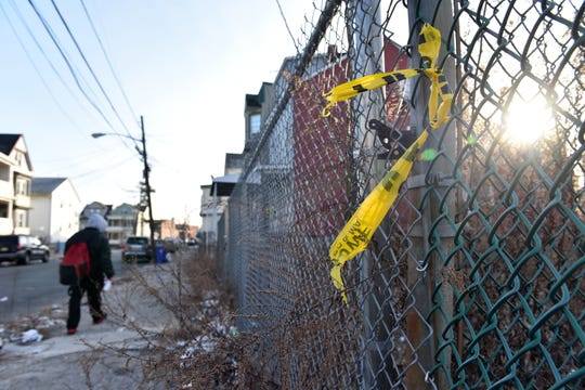 Police tape on a fence and candles on the ground can be seen where a person was killed a shooting on 16th Ave in Paterson, on Wednesday December 19, 2018.