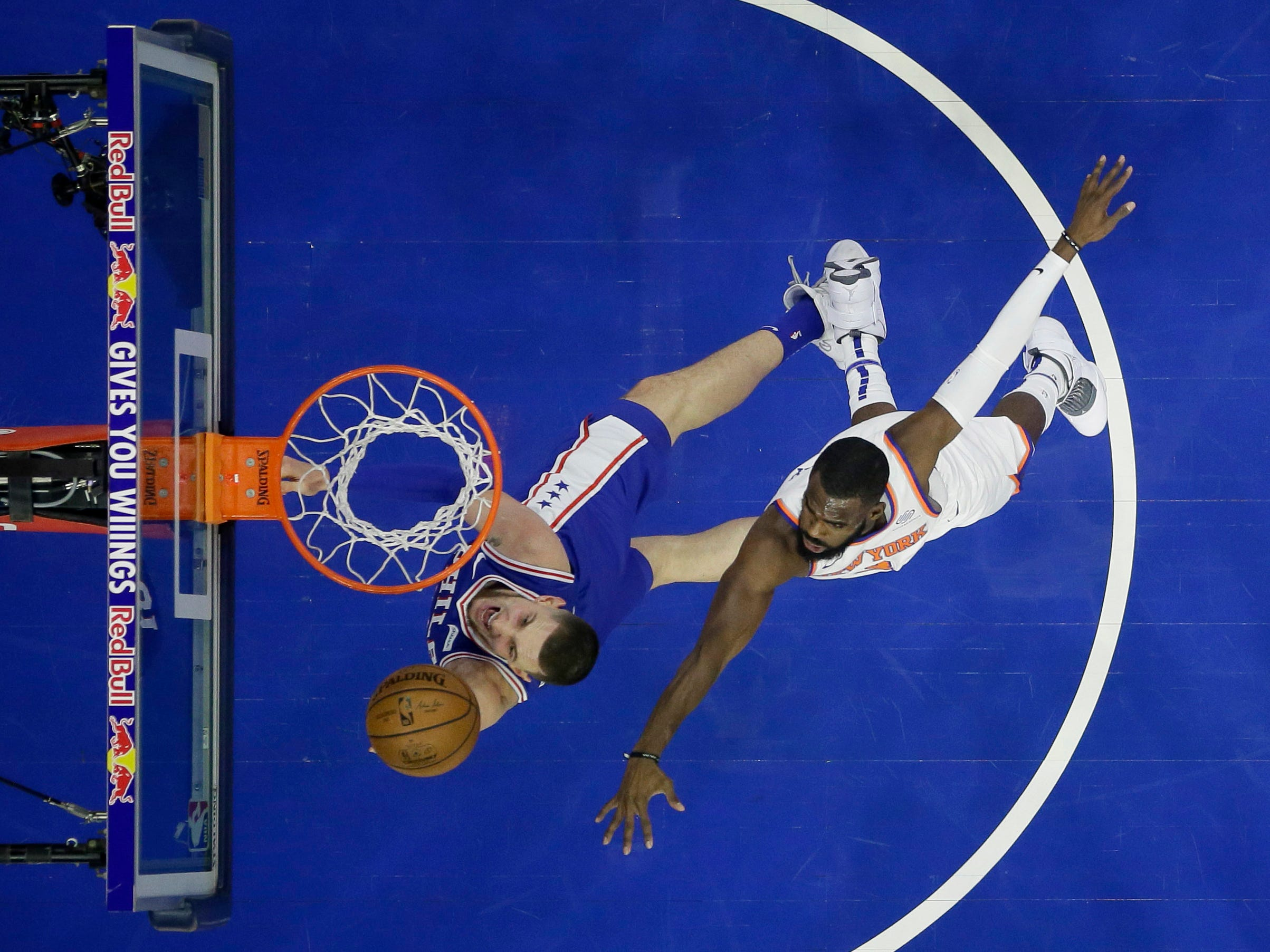 Philadelphia 76ers' Mike Muscala, left, goes up for a shot against New York Knicks' Tim Hardaway Jr. during the first half of an NBA basketball game, Wednesday, Dec. 19, 2018, in Philadelphia.