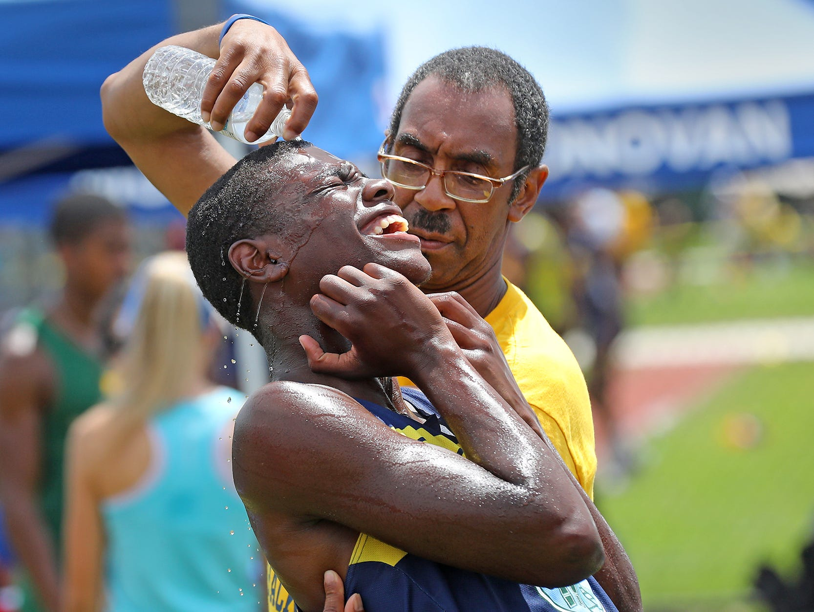 Mekhi Fields of Eagles Academy in Newark who ran the 4x400 meter is cooled off by Eagles Academy teacher Angelo. Clark cool him off after Fields ran his race. Pedota POY 2018