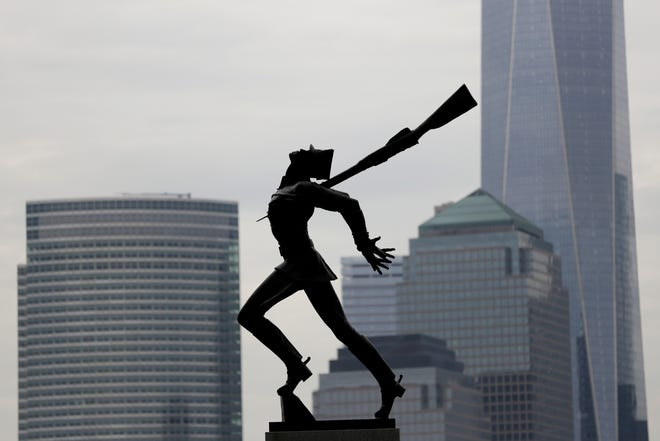 Buildings in Lower Manhattan provide a backdrop to a statue dedicated to the victims of the Katyn massacre of 1940, in Jersey City, N.J.