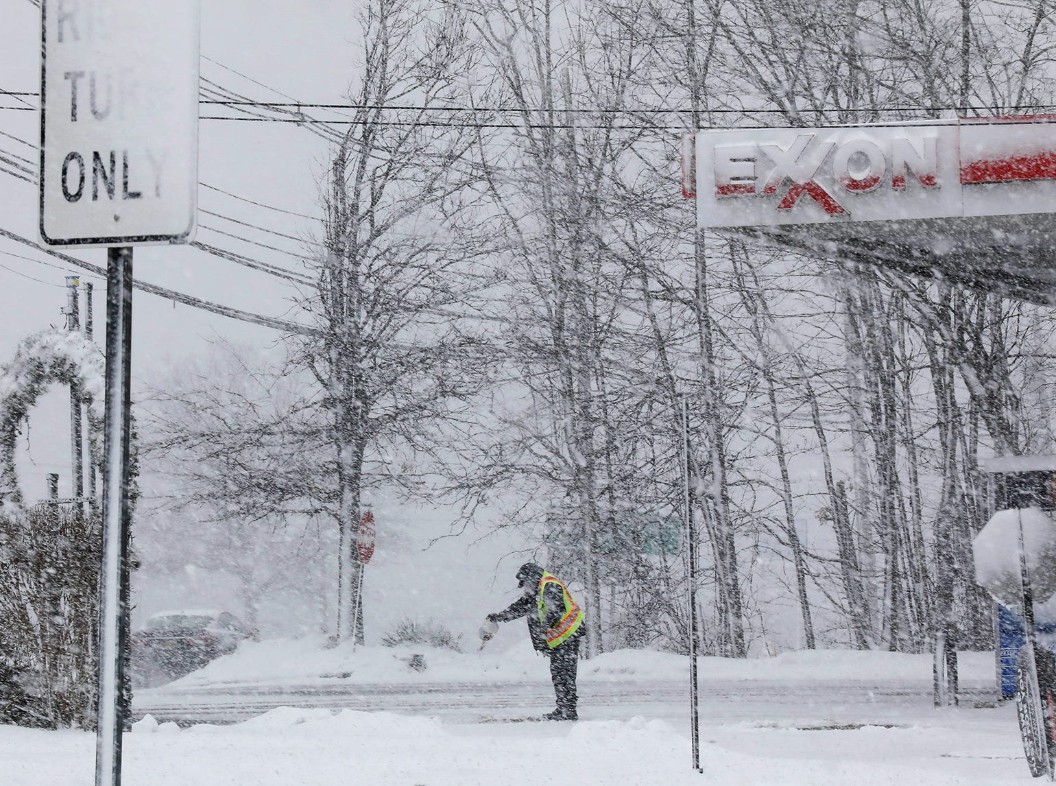 An Exxon station on the southbound side of Route 23 in Wayne at the height of the afternoons snowfall. After shoveling, an attendant drops some salt on the road surface.Pedota POY 2018