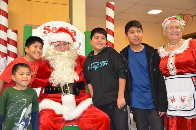 From bottom left, brothers Gustavo, Gael, Gerardo and Angel pose with Santa and Mrs. Claus during a Christmas celebration.