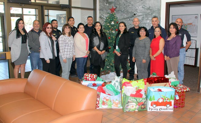 Court Appointed Special Advocates (CASA) and City of Deming Employees are ready to deliver Christmas gifts for 20 foster children under the watchful eye of CASA volunteers and for Bell Elementary School students.