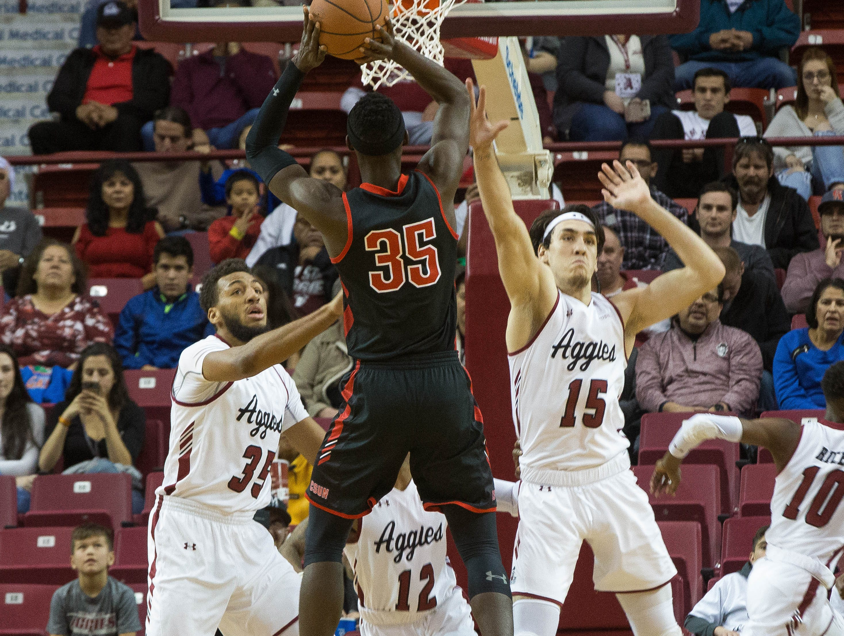 Aggies Johnny Mccants, Ivan Aurrecoechea, attempt to block California State University, Northridge's Lamine Diane, Wednesday December 19, 2018 at the Pan American Center.