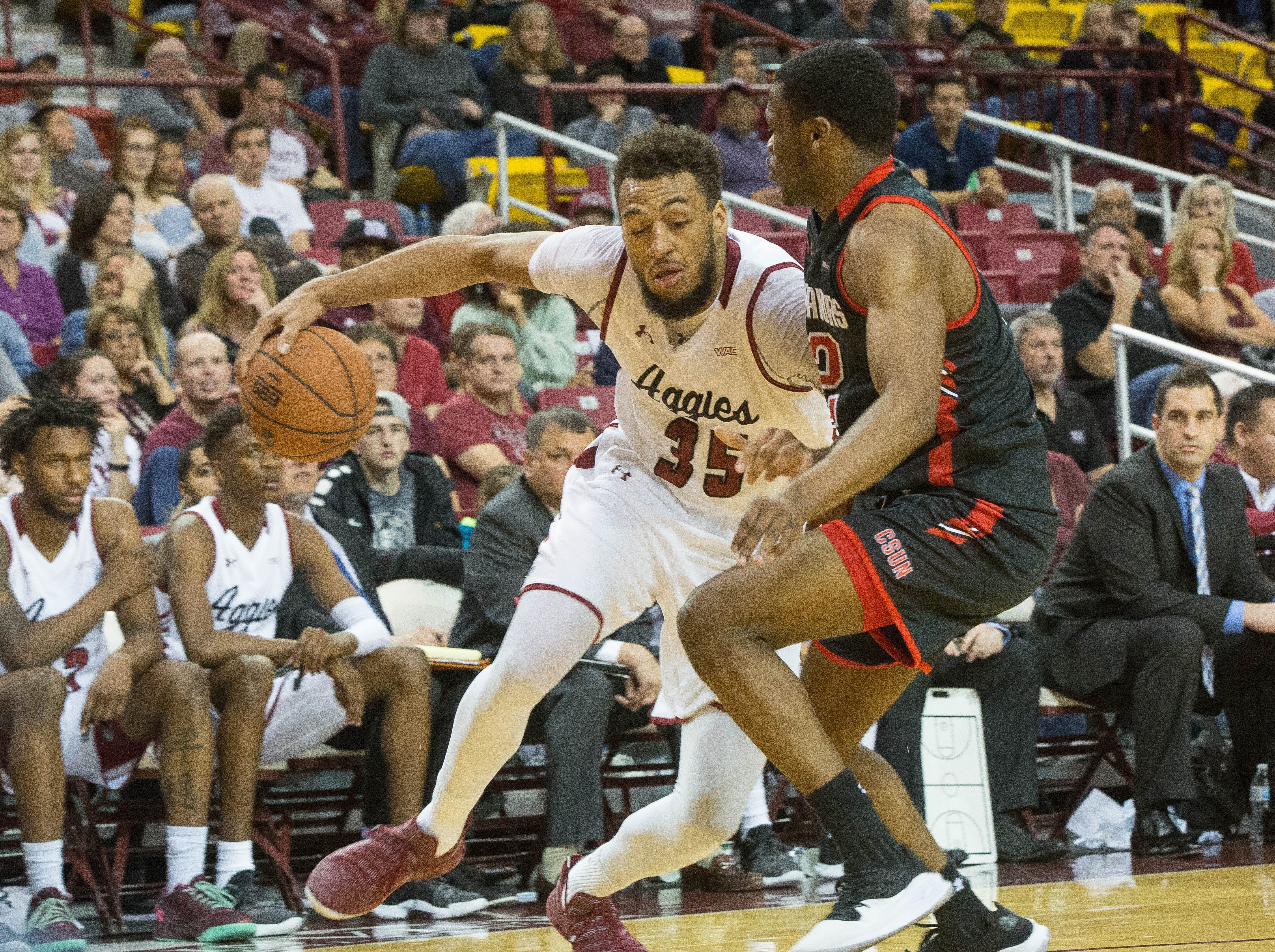 New Mexico State's Johnny Mccants, pushes past California State Univeristy Northridge's Elijah Harkless, during the second half of NMSU's game against CSUN, Wednesday, December 19, 2018 at the Pan American Center. Aggies won 92- 57.