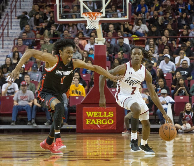 New Mexico State's Terrell Brown, drives down court as California State Univeristy Northridge's Rodney Henderson Jr. guards him, Wednesday December 19, 2018 at the Pan American Center. Aggies won 92 -57.