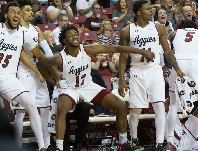New Mexico State's Aggies cheer after teammate, Berrick JeanLouis, dunks the ball over California State Univerisity, Northridge's Lamine Diane during the second half of NMSU's game against CSUN, Wednesday, December 19, 2018. Aggies won 92-57.