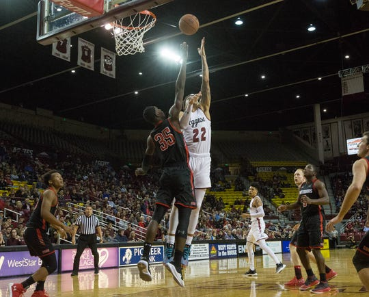 New Mexico State University's Eli Chuhua shoots a lay up over California State University Northridge's Lamine Diane, on Wednesday at the Pan American Center.