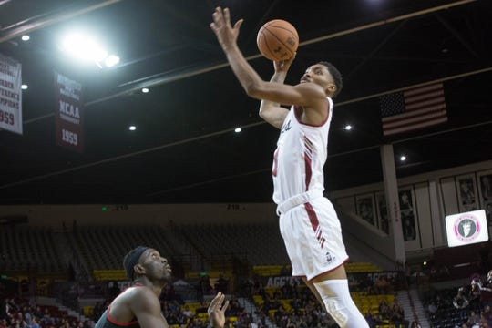 New Mexico State's Berrick JeanLouis, dunks the ball over California State Univerisity, Northridge's Lamine Diane during the second half of NMSU's game against CSUN, Wednesday, December 19, 2018. Aggies won 92-57.