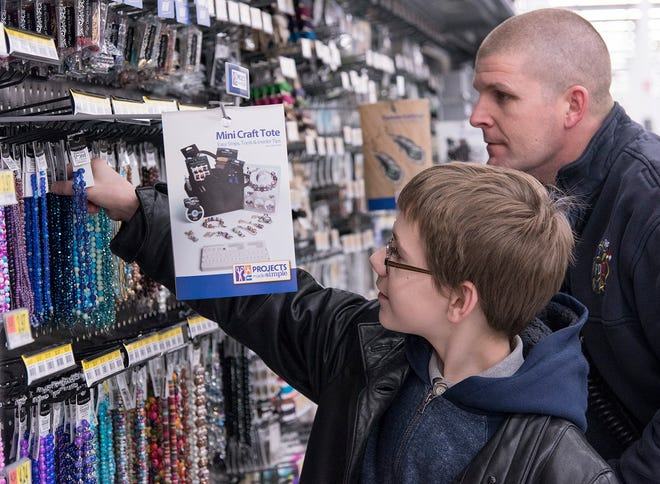 Xander McDevitt, thirteen years old, says his mom likes crafts, so craft items are what he's looking for, with help from Lyon Twp Fire Department Sgt Reggie Madeline.
