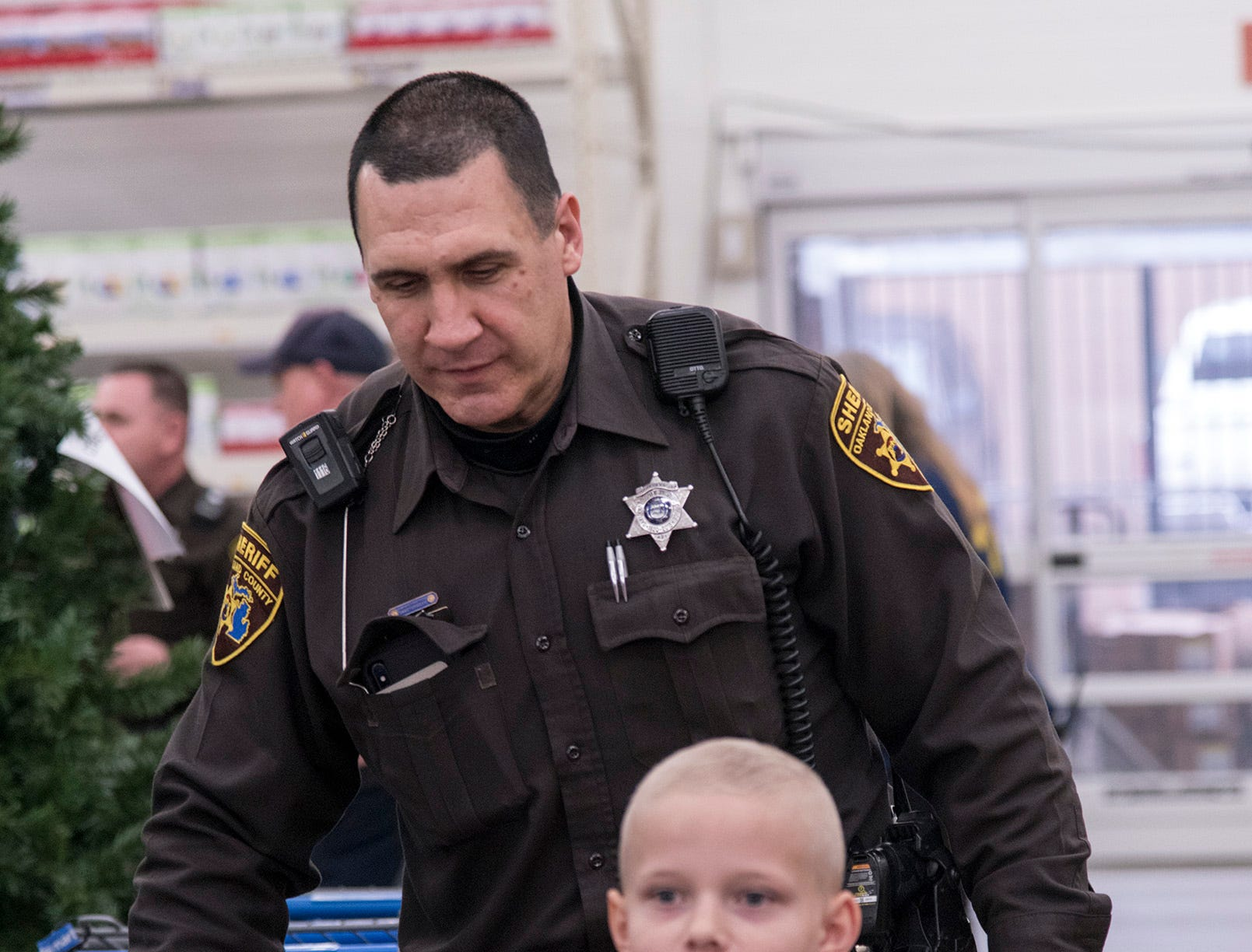 Oakland County Sheriff Deputy Tom Biggers and nine year old Jayden Paradis head out for some holiday shopping.
