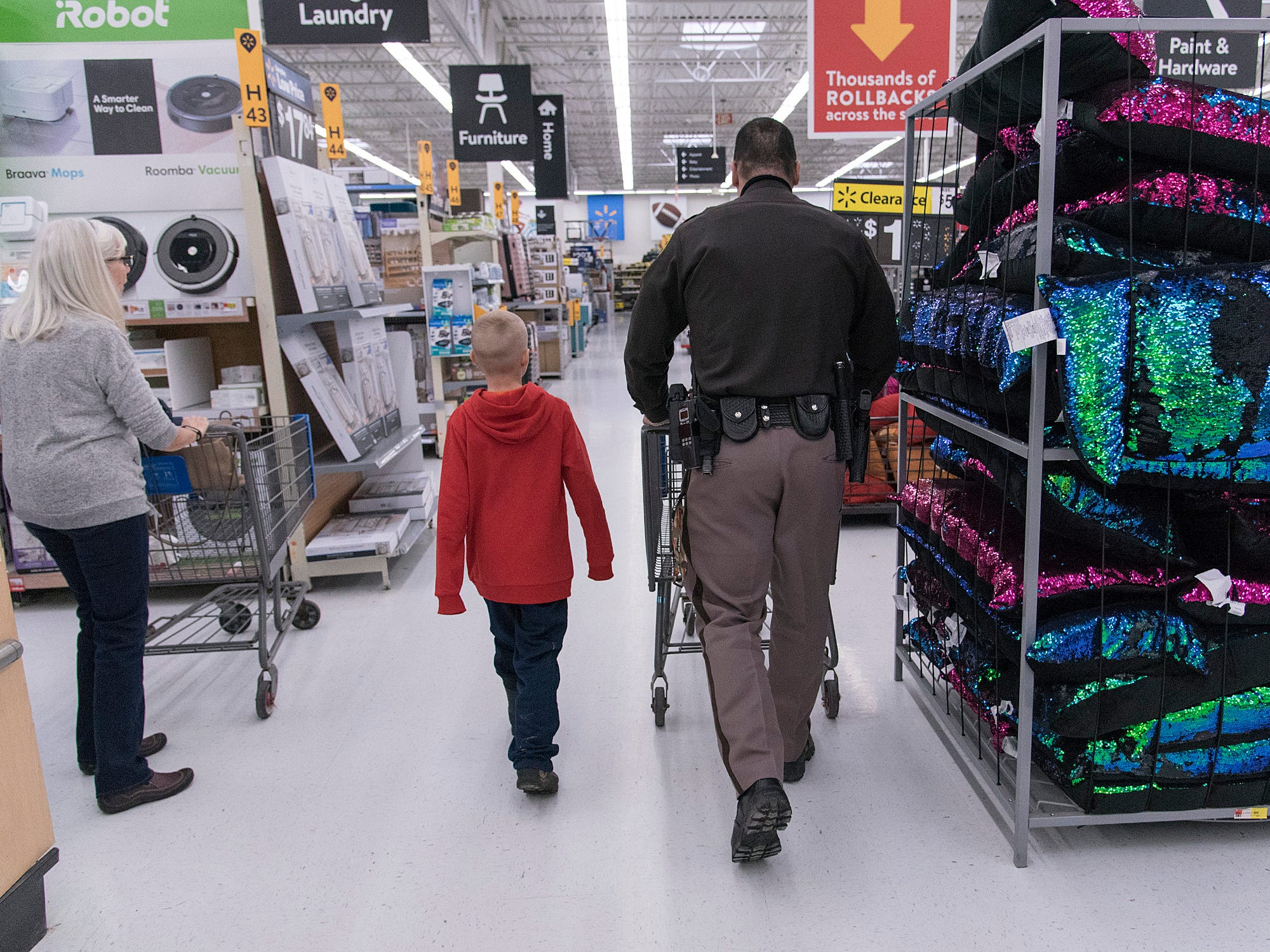 Oakland County Sheriff Deputy Tom Biggers and nine year old Jayden Paradis head out for some holiday shopping at Walmart in New Hudson..