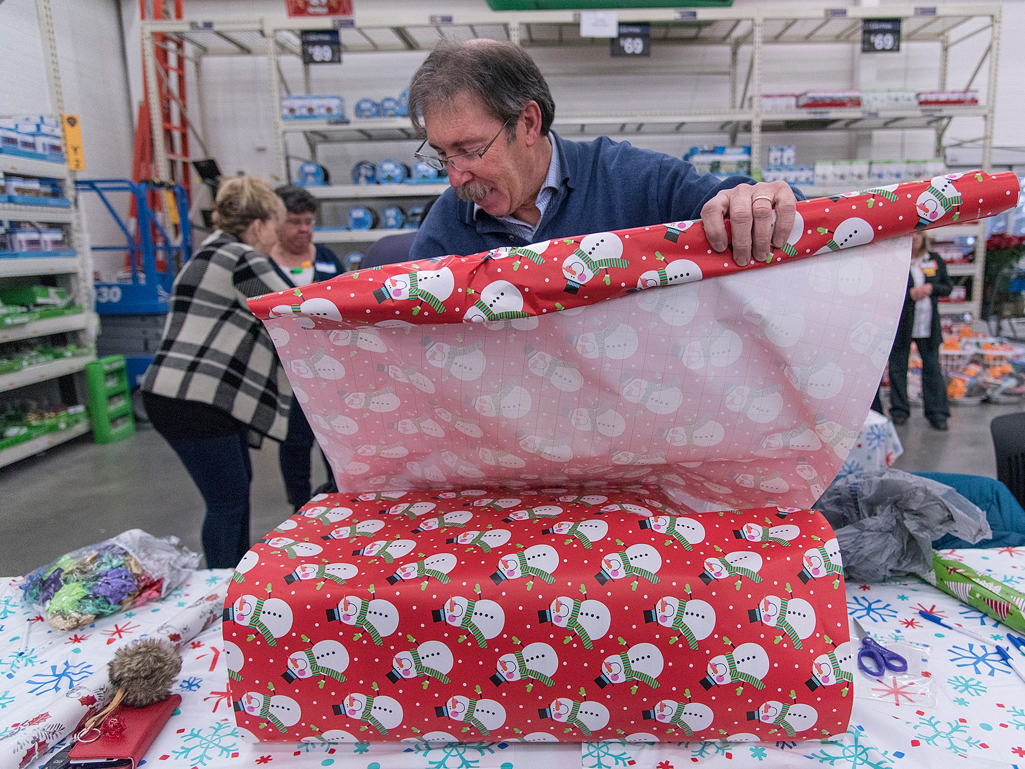 County Commissioner Phil Weipert volunteered to wrap gifts.