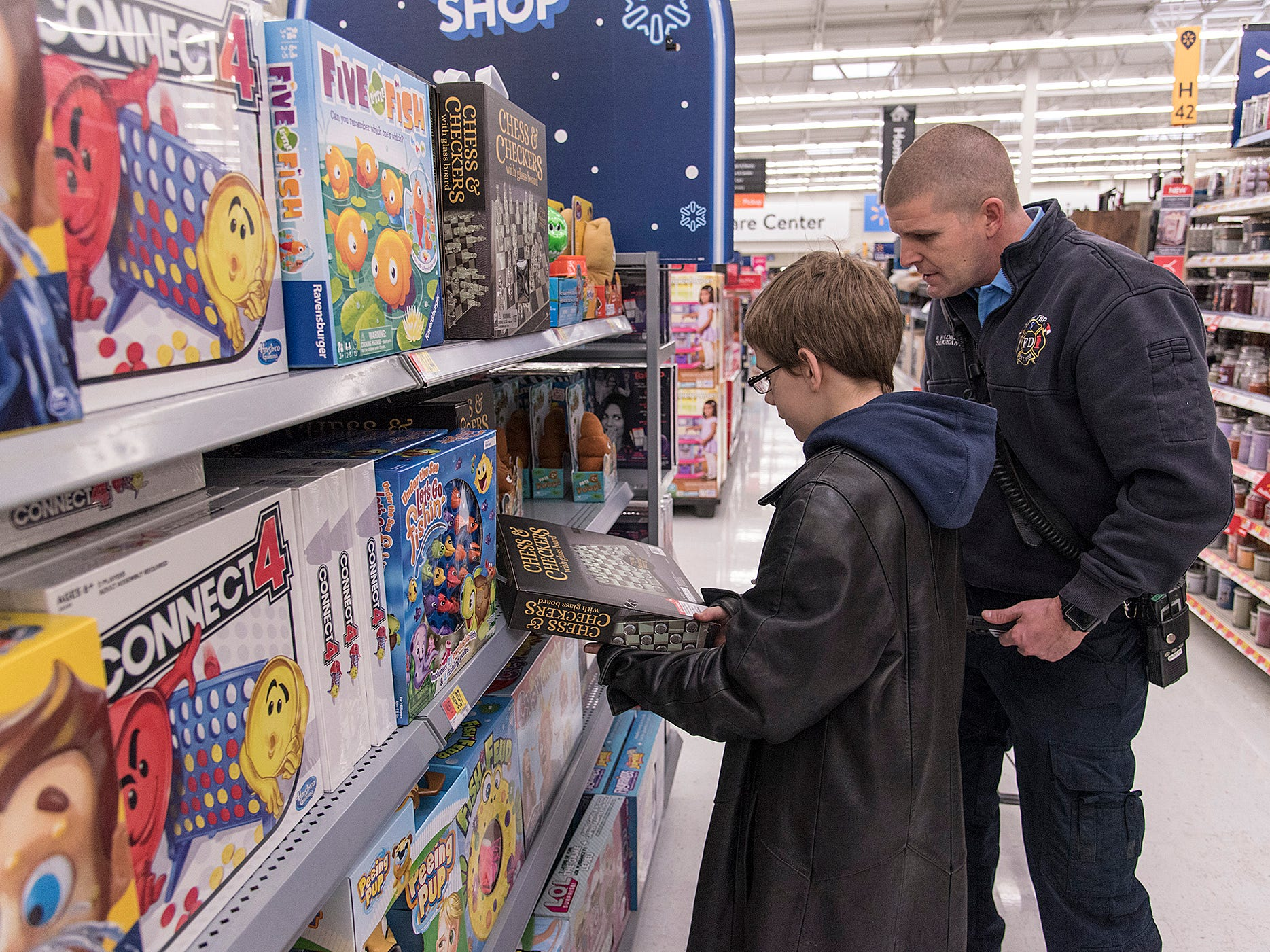 Xander McDevitt and Lyon Twp Fire Department Sgt Reggie Madeline look for a board game for Xander's family.