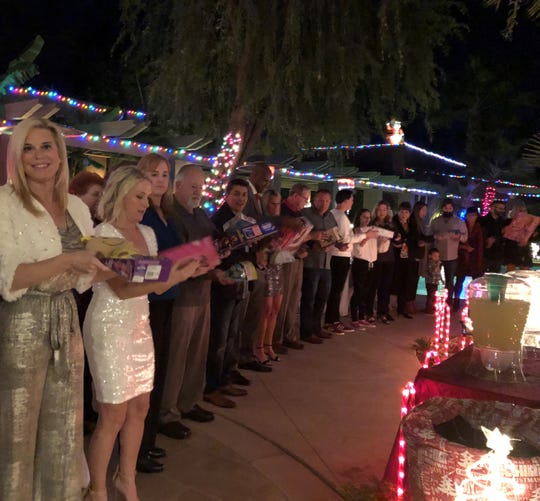 Hostess Susan Winters-McIntosh leads the conga line of guests passing gifts.