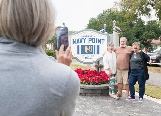 Pam Clyde snaps a photo Thursday of, from left, Michelle Gray, Bill Norvell and Pat Page in front of the new Navy Point neighborhood entrance plaza in Pensacola.