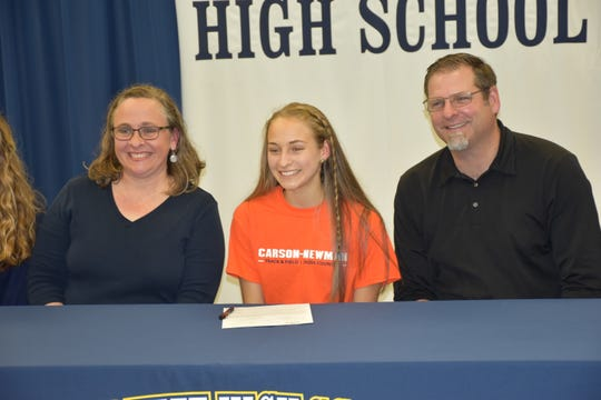 Gulf Breeze senior Hannah Spooneybarger, center, with her parents, Shannon and Jeff, after she had a celebration event Dec. 13 at the school for signing in mid-November with Carson-Newman during the NCAA early signing period.