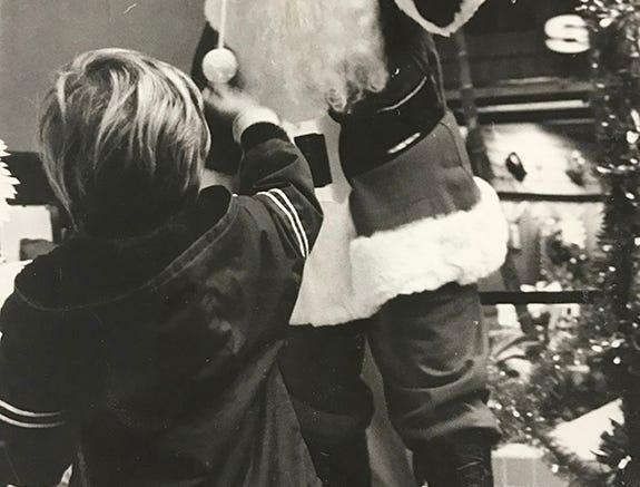 A boy waves at Santa Claus at Cordova Mall, 1974