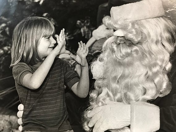 A deaf girl signs her Christmas wish list to Santa Claus, 1984. Both she and Santa are deaf.