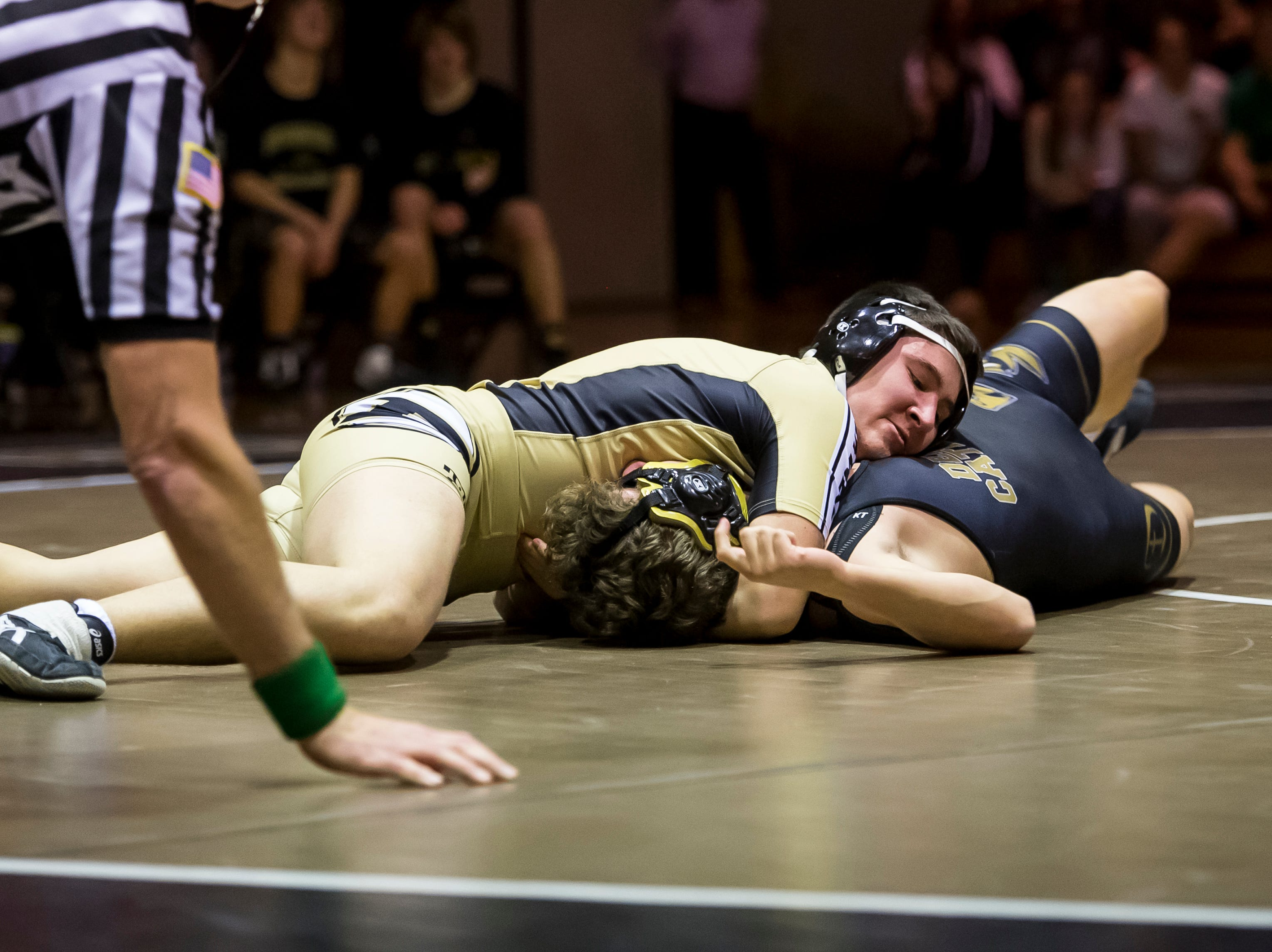 Biglerville's Alex Cook works to pin Delone Catholic's Kyle Denisch in the 170-pound bout at Delone Catholic High School on December 19, 2018. The Canners won 51-21.