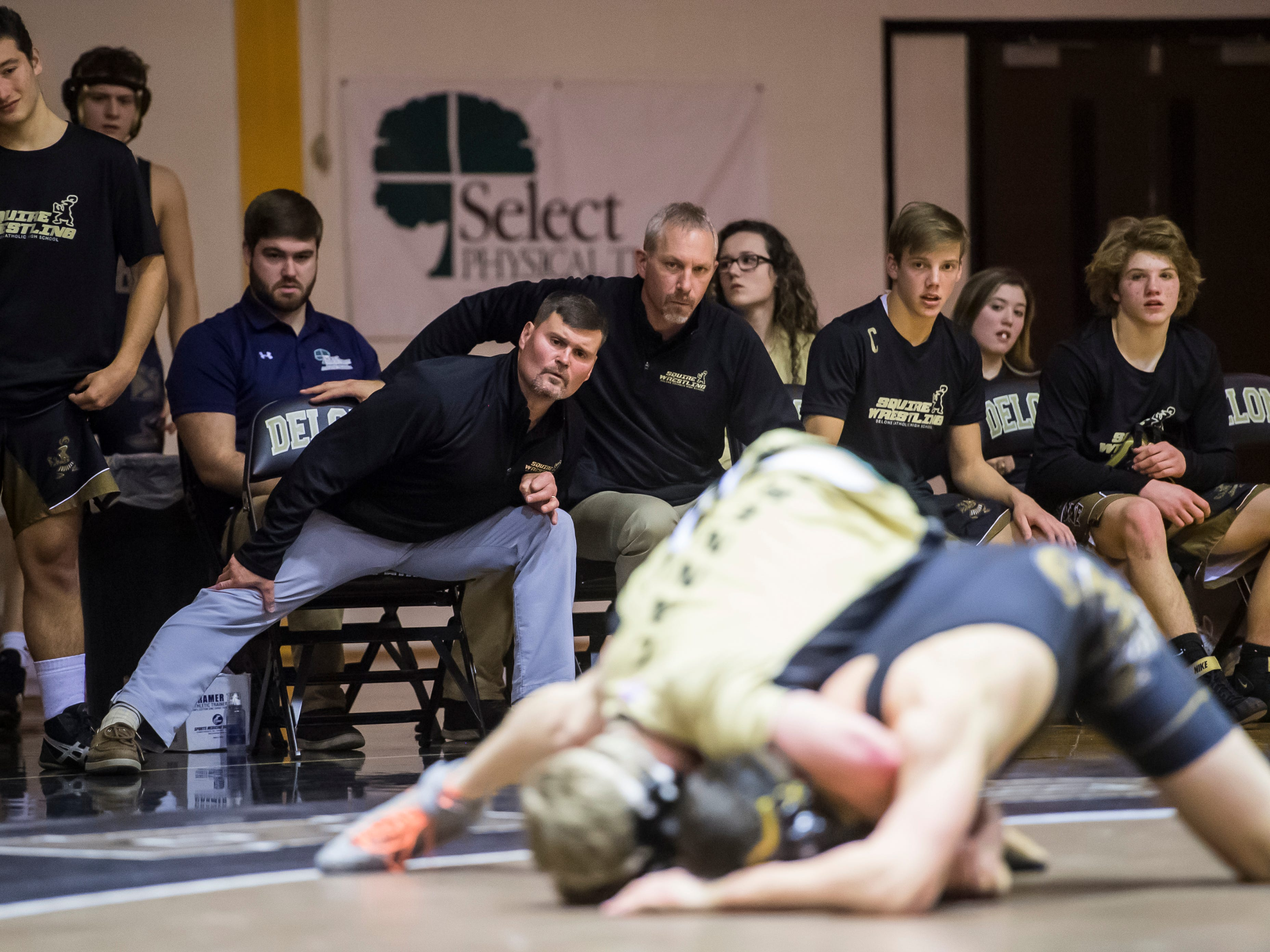 The Delone Catholic bench watches as the Squires' Robert Partenza wrestles Biglerville's Tristan Metzger in the 160-pound bout at Delone Catholic High School on December 19, 2018. Partenza won 11-6 but the Canners won the duel 51-21.