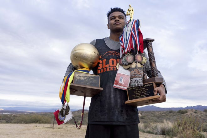 Globe senior basketball player B.J. Burries, who is on the verge of becoming the state's all-time leading scorer, poses with his many accolades his home on the San Carlos Apache Indian Reservation.