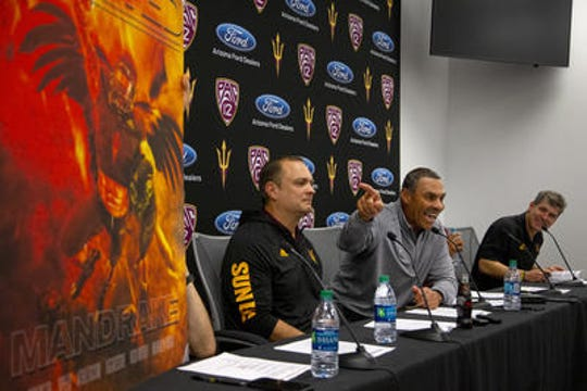 ASU football coach Herm Edwards points to poster of his mythical recruiting ideal Mandrake during signing day press conference Wednesday.