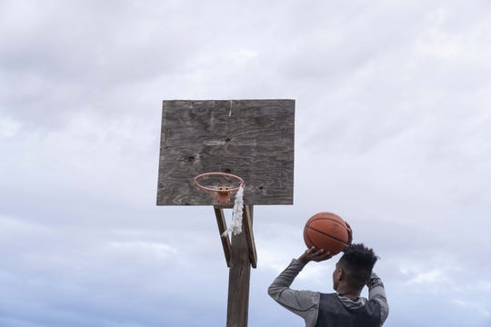 Globe senior basketball player B.J. Burries, who is on the verge of becoming the state's all-time leading scorer, shoots on a hoop at his home on the San Carlos Apache Indian Reservation.