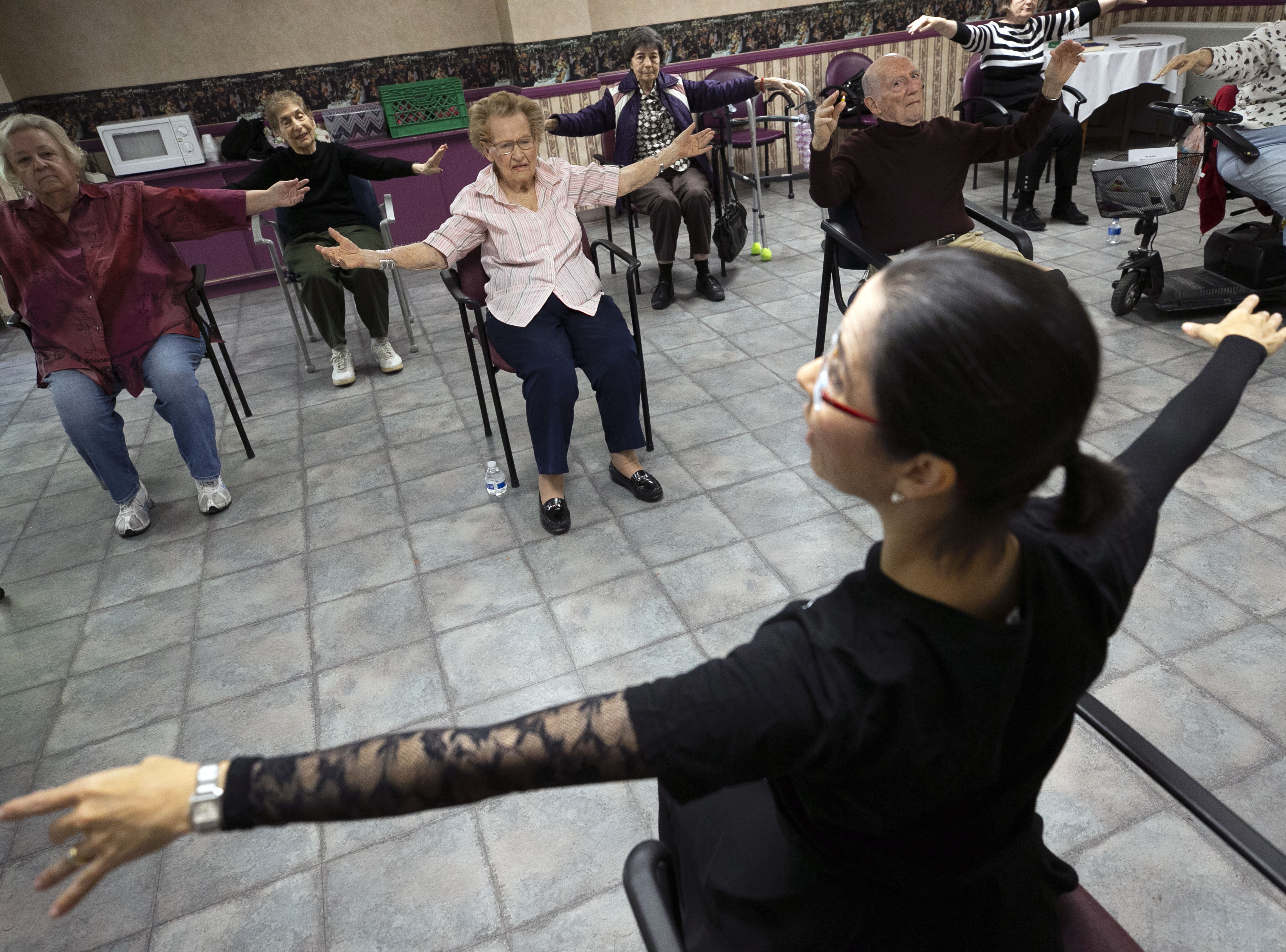 Fabiola Ambrosio, a faculty member with Ballet Arizona, leads a ballet class with Betty Benyes (top center), 100, and other participants during Ballet Arizona's Creative Aging class at the Jewish Family & Children's Service Center for Senior Enrichment in the Palazzo Assisted Living Facility in Phoenix on Nov. 27, 2018.
