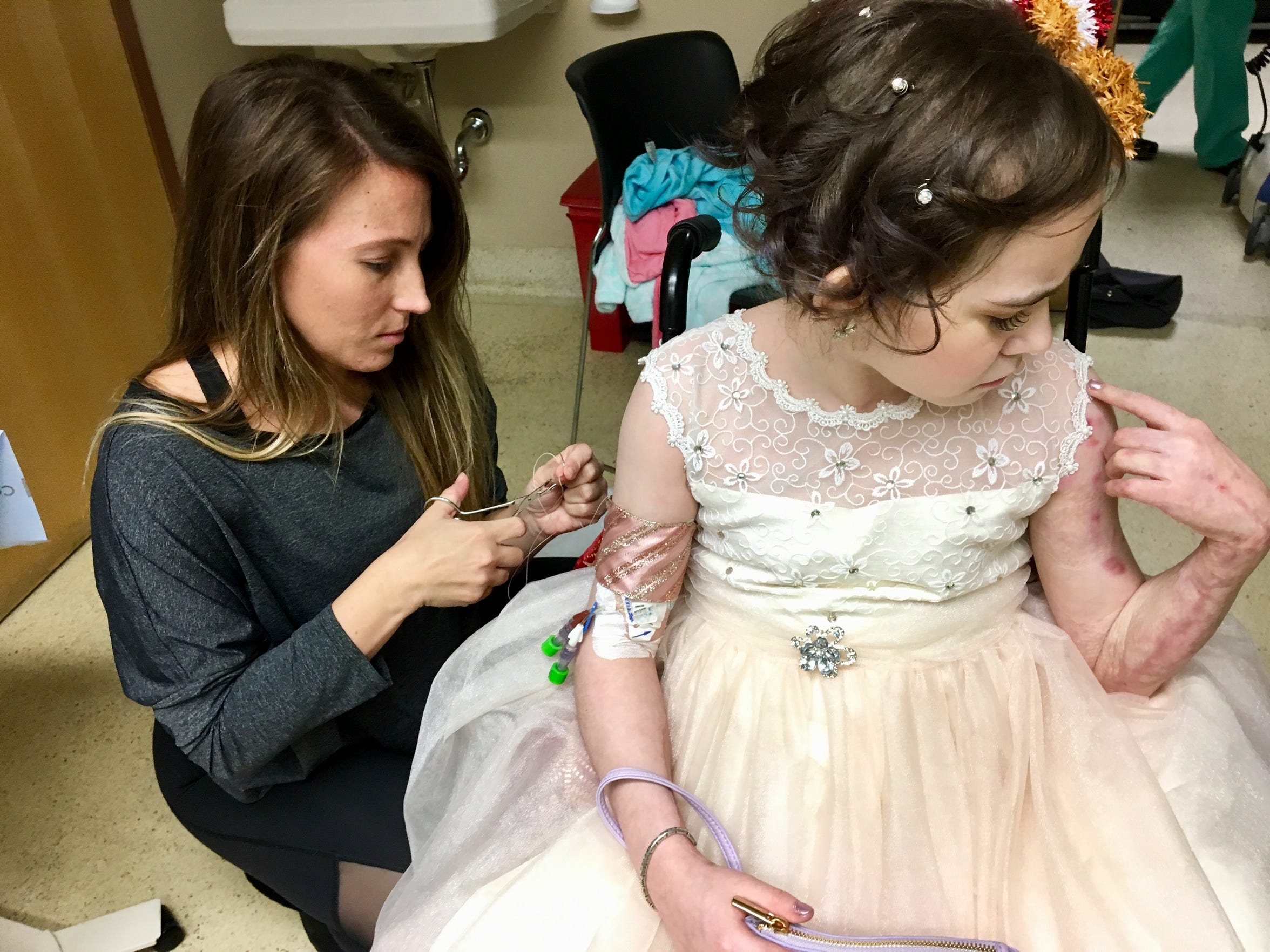 "Physician resident Emily Helmick covers Isabella McCune's the PICC line, a catheter tube in her right arm, with a ribbon, stitching it closed with a suture needle. ""You know how to sew?"" Isabella asked. ""Skin,"" Helmick said, making Isabella giggle."