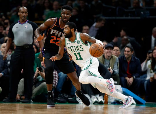 Celtics guard Kyrie Irving drives past Suns center Deandre Ayton during the first quarter of a game Dec. 19 at TD Garden.