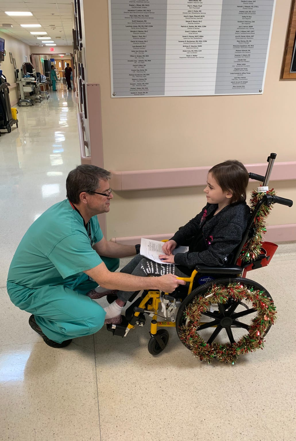 Dr. Kevin Foster, head of the Arizona Burn Center in Phoenix, says goodbye to 9-year-old Isabella McCune as she leaves after nine months in his care. The doctor pushed her wheelchair out to her parents' car.