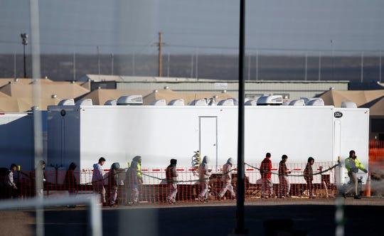 Jovencitos menores de edad esperan en fila dentro del Campo de Detención en Tornillo, Texas.