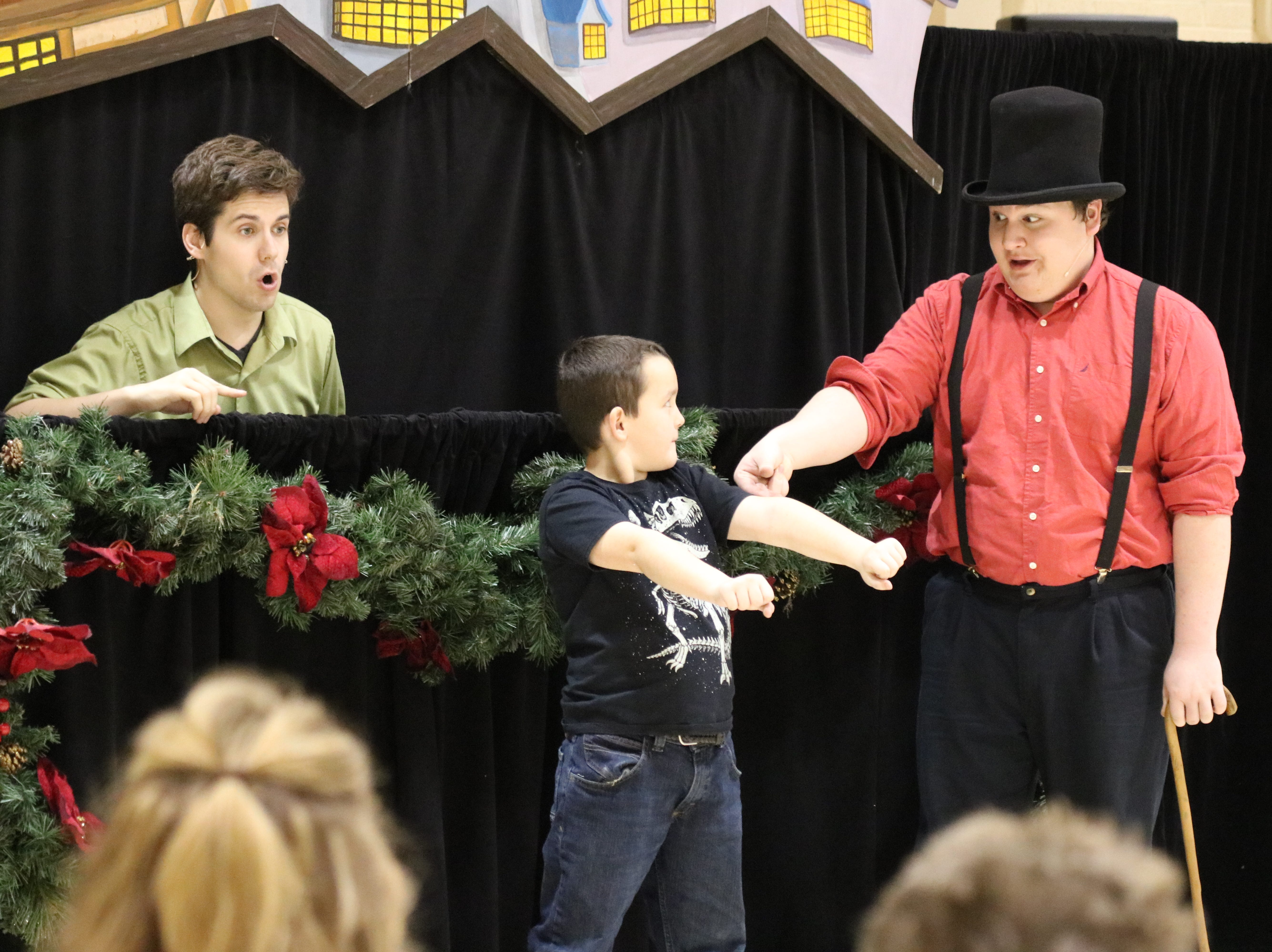 "Adam Myosky, a third grade student at ICS, helps Brandon Leatherland and Zach Robinson, of Madcap Puppets, perform a scene from ""A Christmas Carol"" on Thursday."