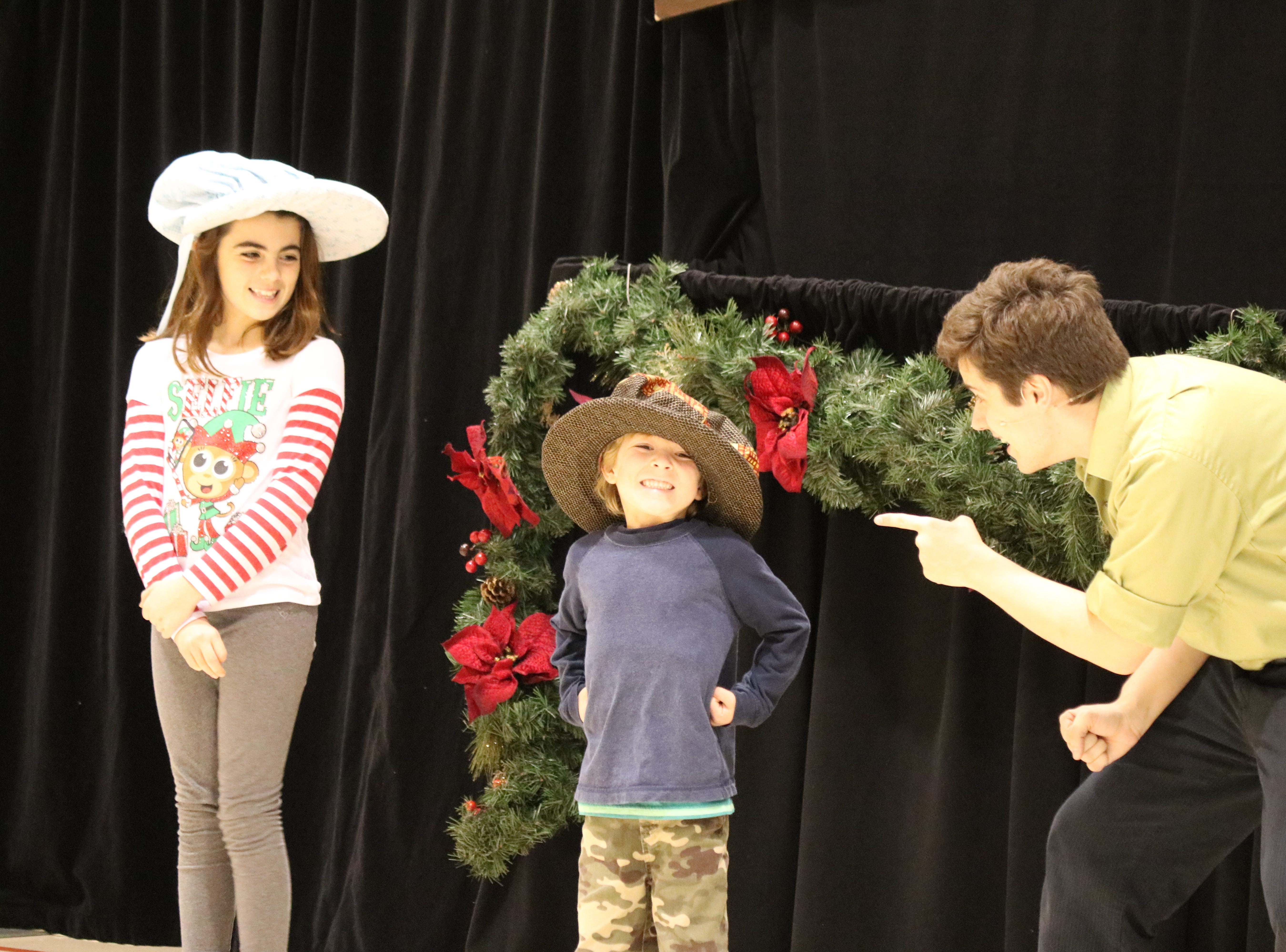 "Rachel Spicer and Leo Avis, students at Immaculate Conception School, help Madcap Puppets perform a scene from ""A Christmas Carol"" on Thursday."